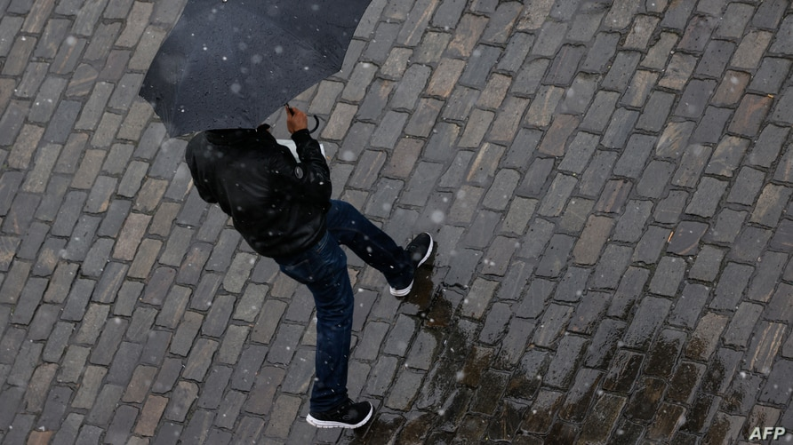 FILE - A man shelters under an umbrella as snow turns to sleet and rain in Berlin, Germany, May 7, 2021.