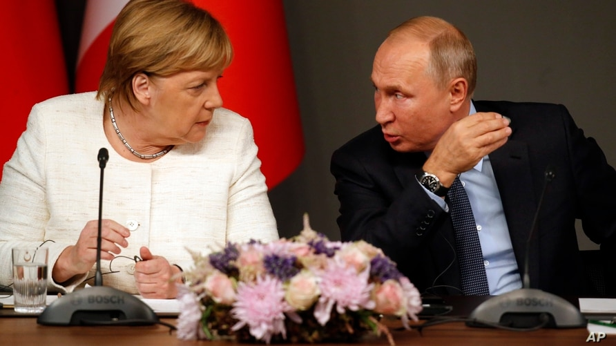 German Chancellor Angela Merkel, left, listens to Russian President Vladimir Putin as they attend a news conference following a…
