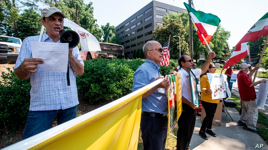 Demonstrators chant in front of a polling place for Iranian Americans taking part in Iran's presidential elections on Friday,…