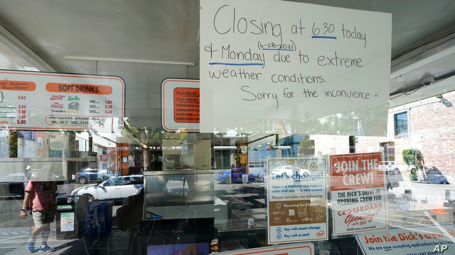 A sign in the window of the Dick's Drive-In in Seattle's Capitol Hill neighborhood is shown Monday, June 28, 2021, in Seattle…
