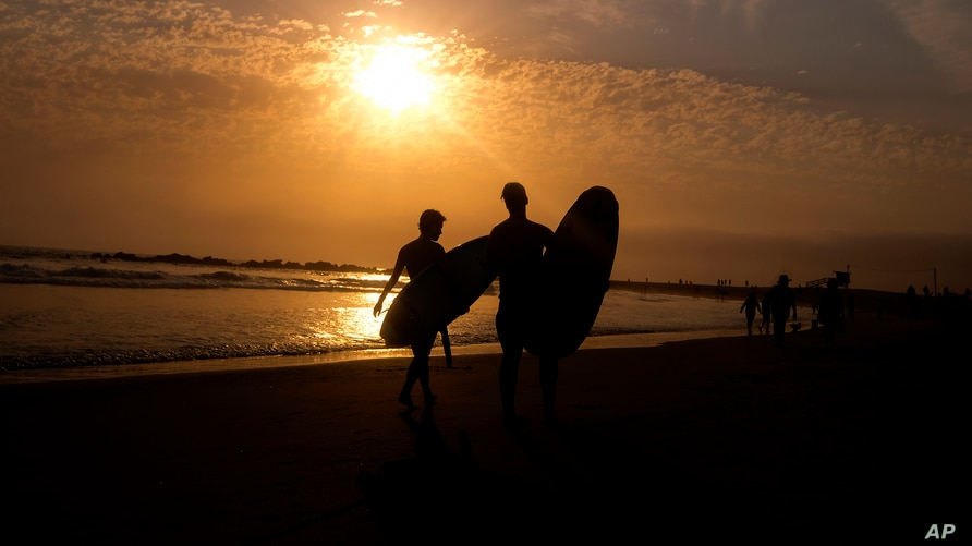 FILE - Surfers are silhouetted during sunset in the Venice Beach section of Los Angeles, California, June 16, 2021. An unusual heat wave is forecast for the coming week for northern California and other parts of the U.S. Pacific Northwest.