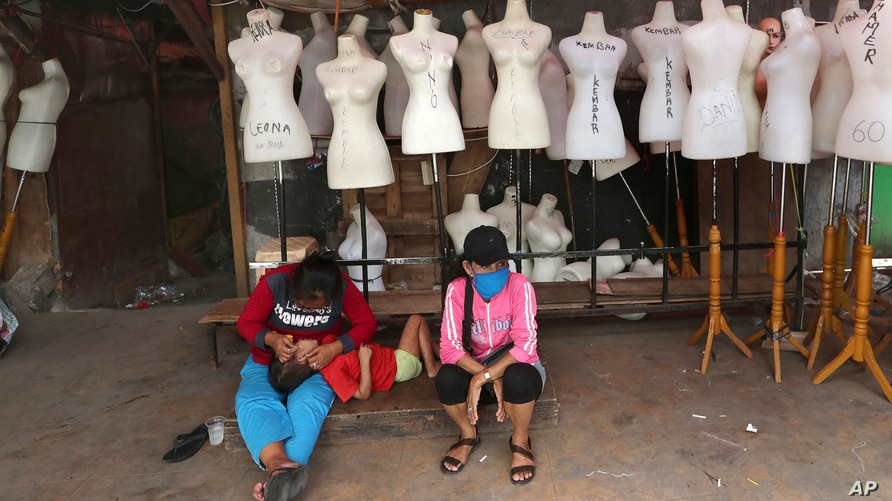 FILE - Women sit in front of mannequins at a textile market shuttered due to the coronavirus pandemic, in Jakarta, Indonesia, April 30, 2020.