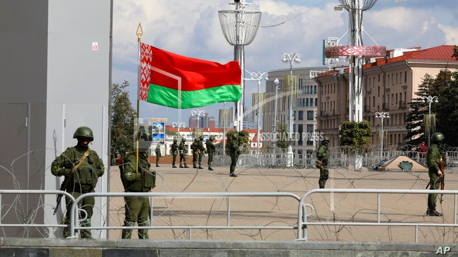 FILE - Belarusian Internal Ministry troops, with one soldier holding a Belarusian flag, guard a central area in Minsk, Belarus, Sept. 13, 2020.