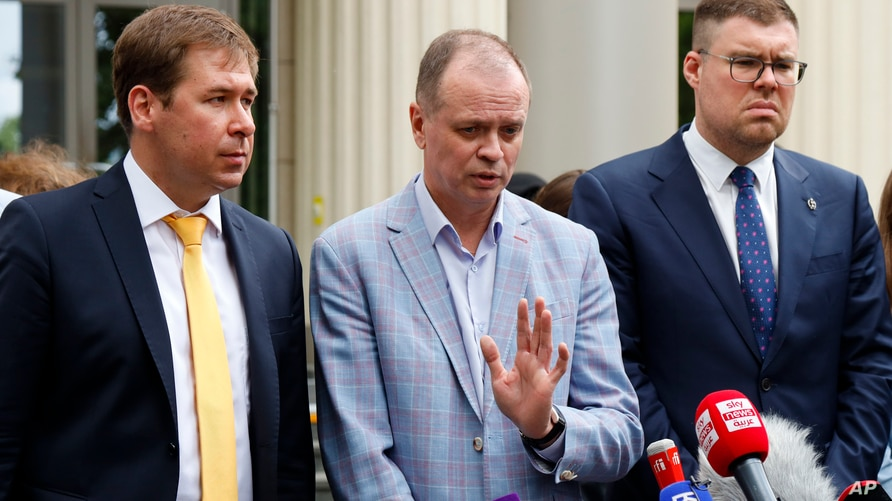 Russian lawyer Ivan Pavlov, center, speaks to the media as lawyers Ilya Novikov, left, and Vladimir Voronin, right, listen in front of Moscow Court in Moscow, June 9, 2021.