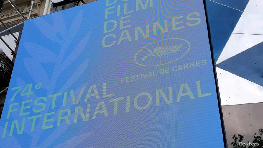 The official logo with a Palme d'Or symbol is seen on a screen in front of a cinema before the presentation of the official selection of the 74th Cannes International Film Festival in Paris, France, June 3, 2021.