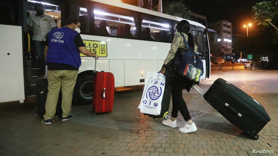FILE - A migrant domestic worker from Africa pulls her luggage toward a bus that will take her with others to the airport to travel back to their home countries, in a Beirut suburb, Lebanon, Oct. 5, 2020.
