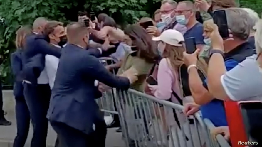 French President Emmanuel Macron is protected by a security officer after getting slapped by a member of the public during a visit to Tain-L'Hermitage, France, in this still image taken from video on June 8, 2021. (BFMTV/ReutersTV via Reuters)