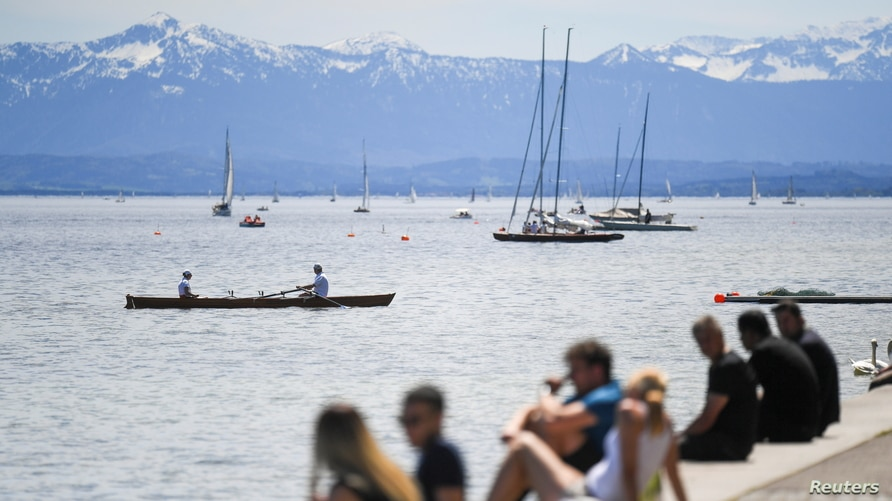 FILE - People enjoy the sun at the shore of Lake Starnberg, in Starnberg, near Munich, southern Germany, May 9, 2021, with the Alps in the background.