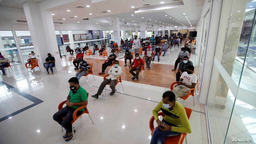 People wait in Sitra Mall to get vaccination against the COVID-19 in Sitra, Bahrain, March 23, 2021.