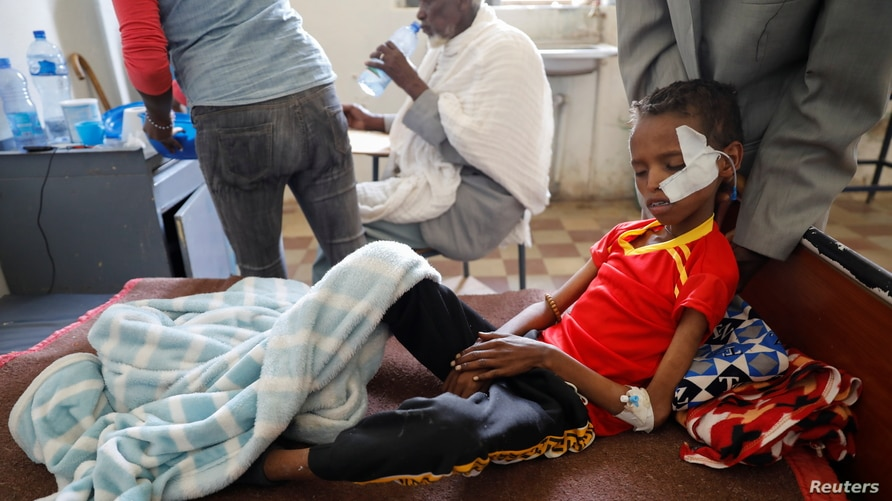 Fourteen-year-old Adan Muez is helped to sit up in his bed at Adigrat General Hospital in the town of Adigrat, Tigray region, Ethiopia, March 18, 2021.