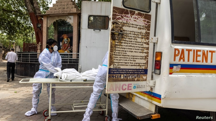 Health workers carry the body of a person, who died from complications related to the COVID-19, for cremation at a crematorium in New Delhi, India, June 10, 2021.