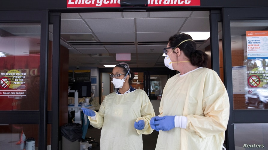 FILE - Nurses talk outside the emergency room at Beaumont Hospital as they manage an influx of COVID-19 cases in Grosse Pointe, Michigan, April 16, 2021.