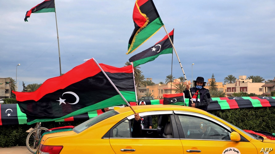 Libyans wave national flags from a yellow cab in the capital Tripoli on February 25, 2021, during celebrations commemorating…
