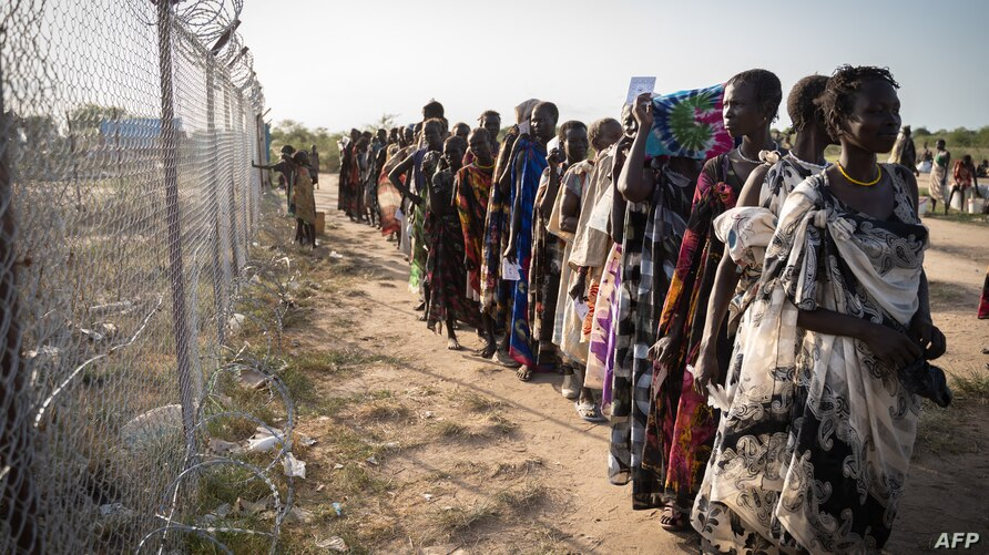 Women from Murle ethnic group wait in a line for a food distribution by United Nations World Food Programme (WFP) in Gumuruk,…