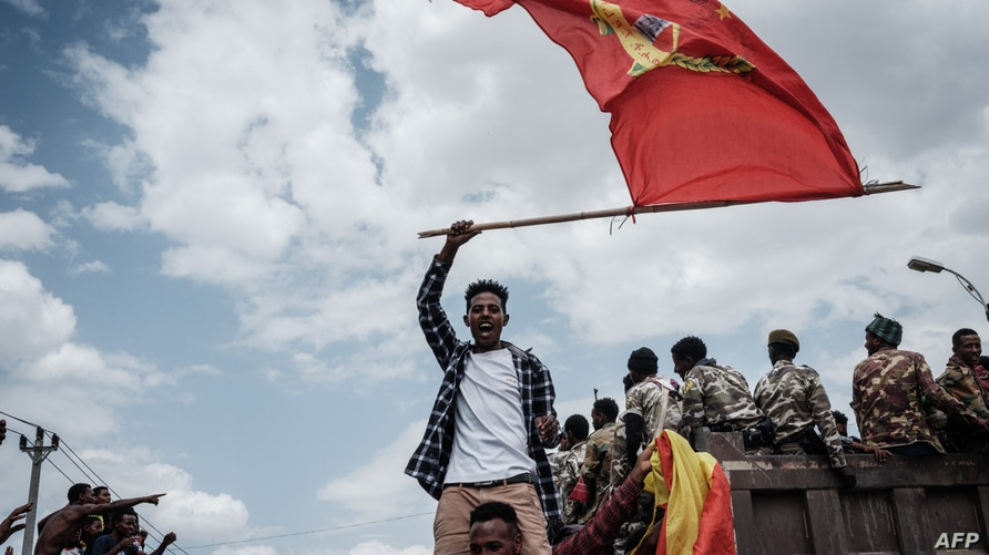 A man waves a Tigray flag as Soldiers of Tigray Defence Force (TDF) return in Mekele, the capital of Tigray region, Ethiopia,…