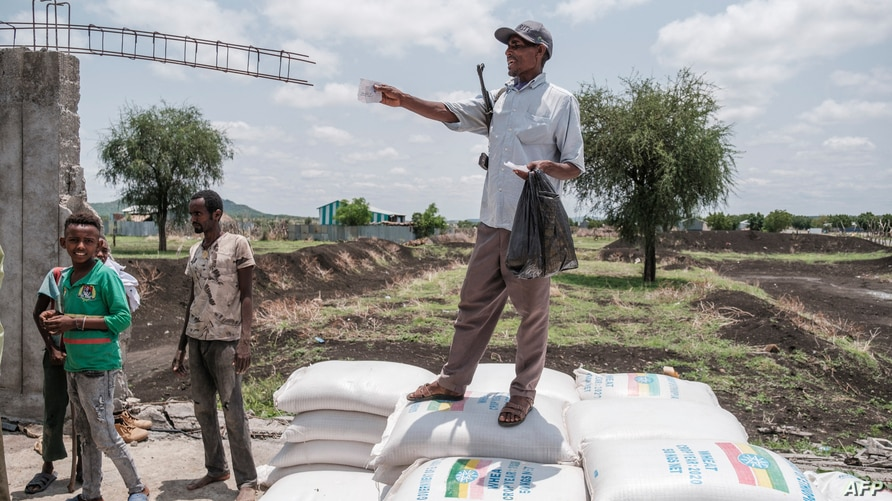 A member of the Amhara militia points out during a food distribution organized by the Amhara government near the village of…