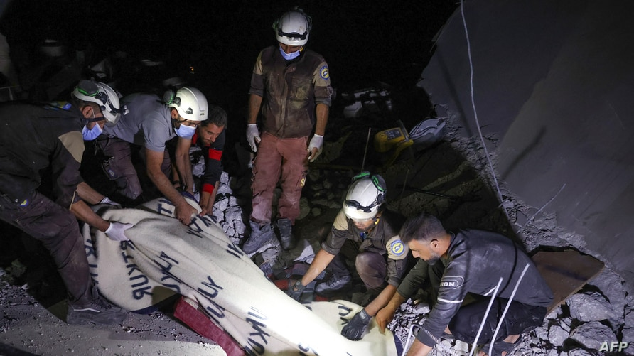 Members of the Syrian Civil Defence (White Helmets) cover the body of a woman with a blanket, as they remove it from the rubble…
