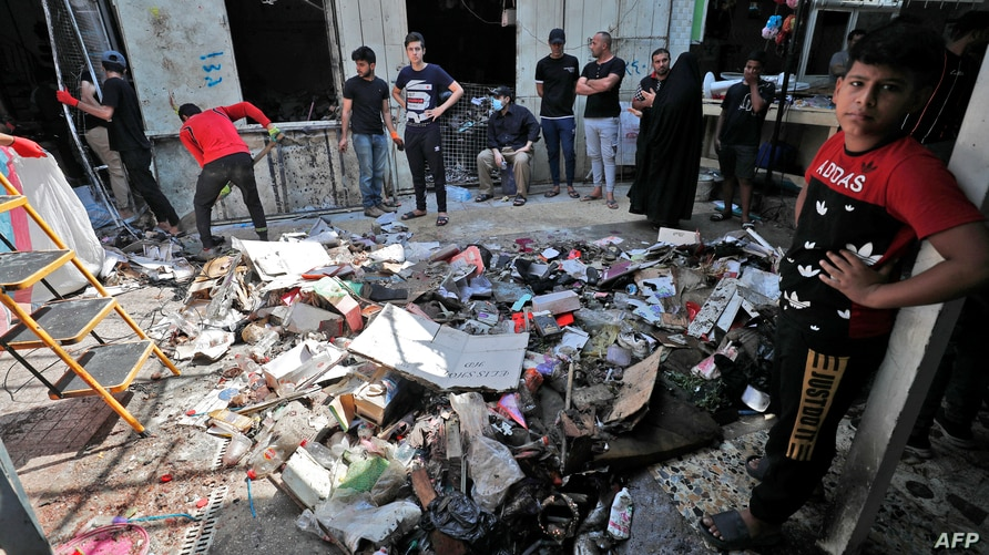 Iraqis inspect the site of the explosion a day earlier in a popular market in the Shiite-majority Sadr City neighbourhood, east…
