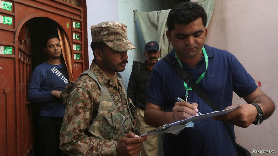 A census enumerator (R) along with a Pakistan Army soldier notes details outside a house during Pakistan's 6th population…