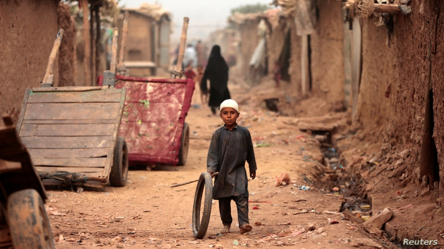 A boy plays with a tyre on an a street in an Afghan refugee camp in Islamabad, Pakistan October 31, 2017.  REUTERS/Caren Firouz