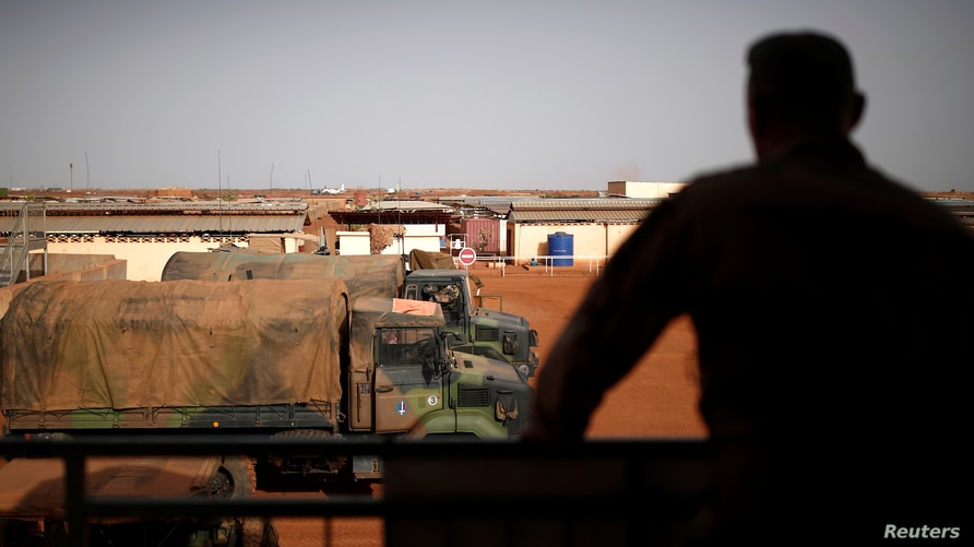 A French soldier is silhouetted as he looks out over Operational Desert Platform Camp (PfOD) during Operation Barkhane in Gao,…