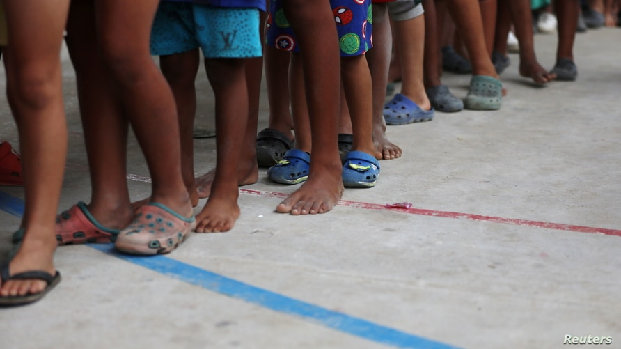 FILE - Venezuelan migrant children line up inside a coliseum where a temporary camp has been set up, after fleeing their country due to military operations, according to the Colombian migration agency, in Arauquita, Colombia, March 26, 2021.