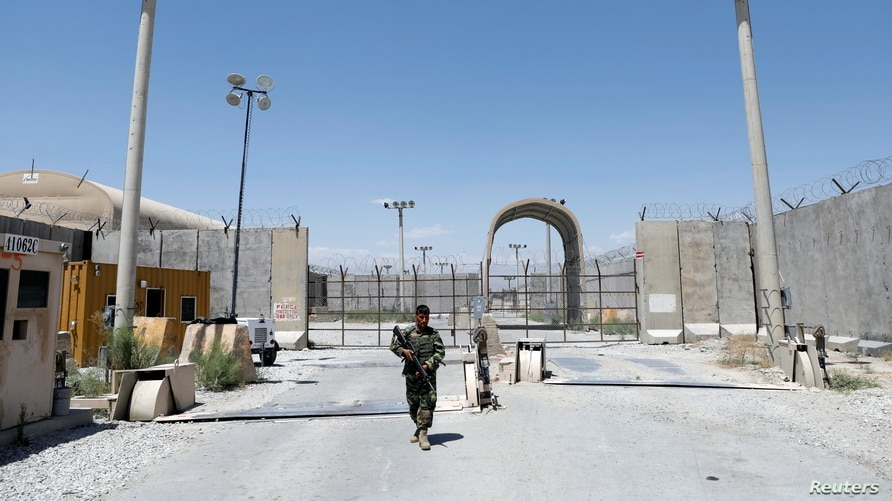 An Afghan National Army soldier stands guard at the gate of Bagram U.S. air base, on the day the last of American troops…