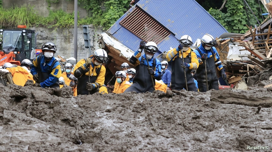 Police officers conduct a rescue and search operation at the site of a mudslide caused by heavy rain at Izusan district in…