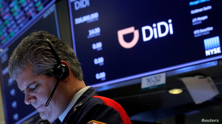 FILE - A trader works during the IPO for Chinese ride-hailing company Didi Global Inc on the New York Stock Exchange (NYSE) floor in New York City, June 30, 2021.