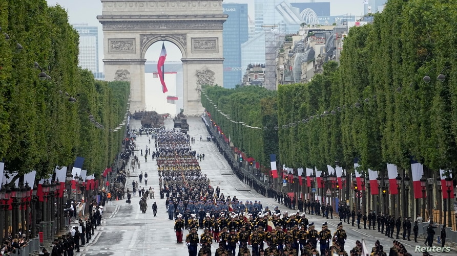 Troops walk down the Champs-Elysees avenue during the Bastille Day parade in Paris, France, July 14, 2021.