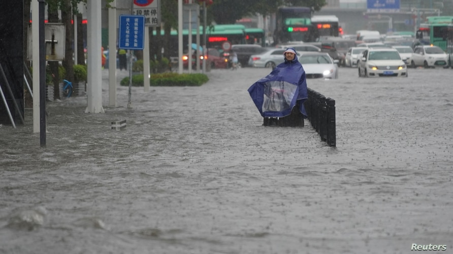 A resident wearing a rain cover stands on a flooded road in Zhengzhou, Henan province, China July 20, 2021. cnsphoto via…