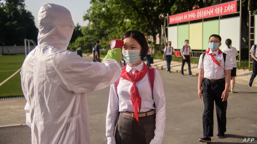 A student has her temperature taken as part of anti Covid-19 procedures before entering the Pyongyang Secondary School No. 1 in Pyongyang, North Korea, June 22, 2021.