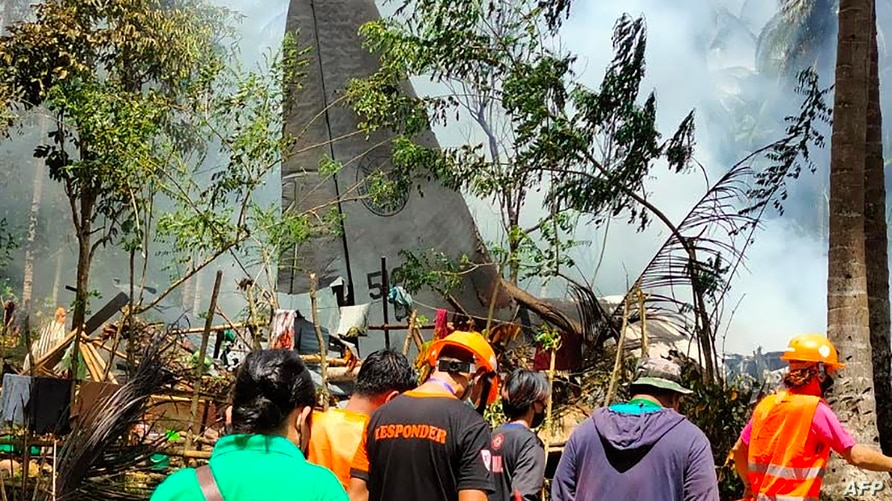 Rescue workers arrive as smoke billows from the wreckage of a Philippine Airforce C-130 transport plane after it crashed in Jolo town, Sulu province on the southern island of Mindanao, July 4, 2021.