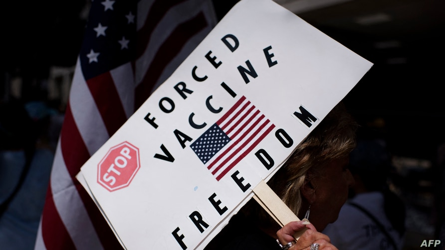 FILE - An anti-vaccine protester holds a sign during a rally outside Houston Methodist Hospital in Houston, Texas, June 26, 2021.