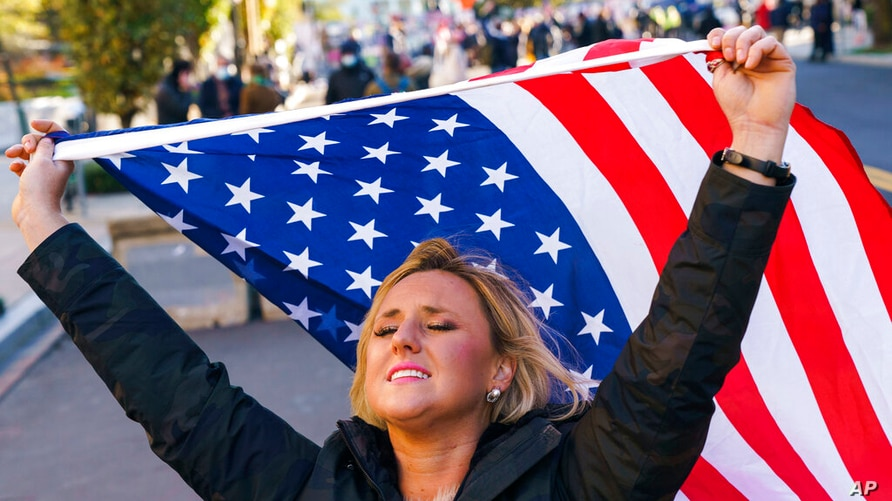 Kelly Janowiak of Chicago, prays with a conservative Christian Evangelical group while holding a American flag, Nov. 2, 2020, in Washington.