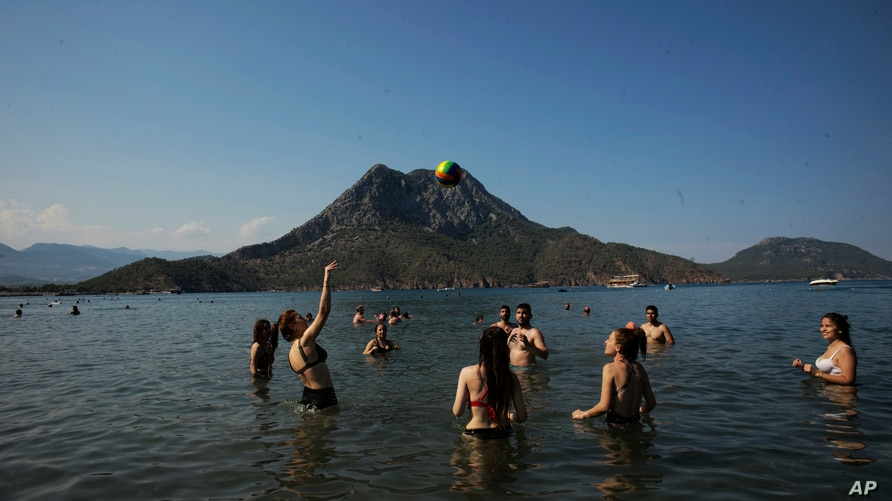 People enjoy the good weather, sea and sun, a day before the Sunday curfew in Adrasan, 100 kilometers west of Antalya, on…