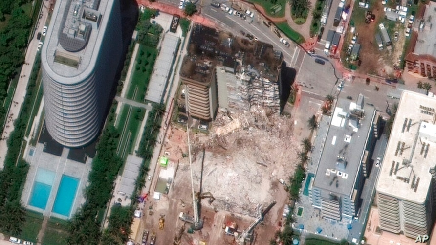 In this satellite image provided by Maxar Technologies heavy-lift cranes are used to aid in the search and recovery operation…