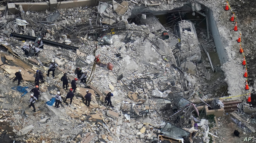 Rescue workers search in the rubble at the Champlain Towers South Condo, in Surfside, Fla, June 26, 2021.