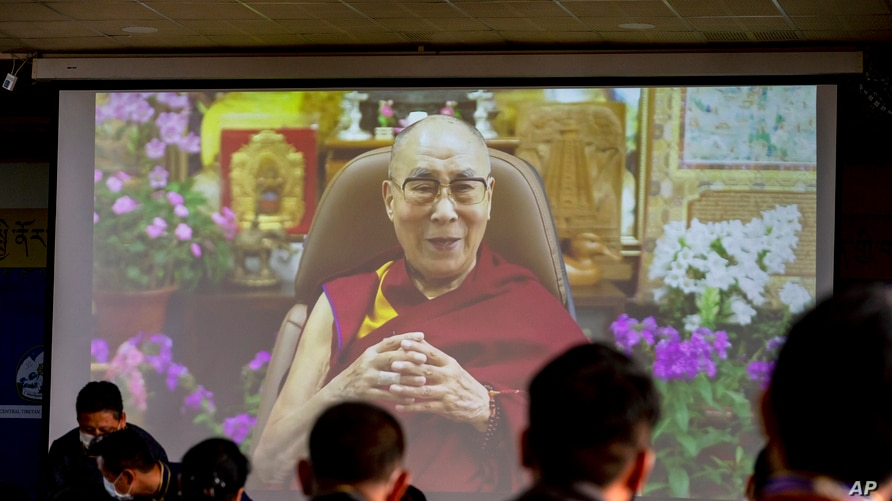 Exile Tibetan government officials watch a message from their spiritual leader the Dalai Lama on a screen during a ceremony