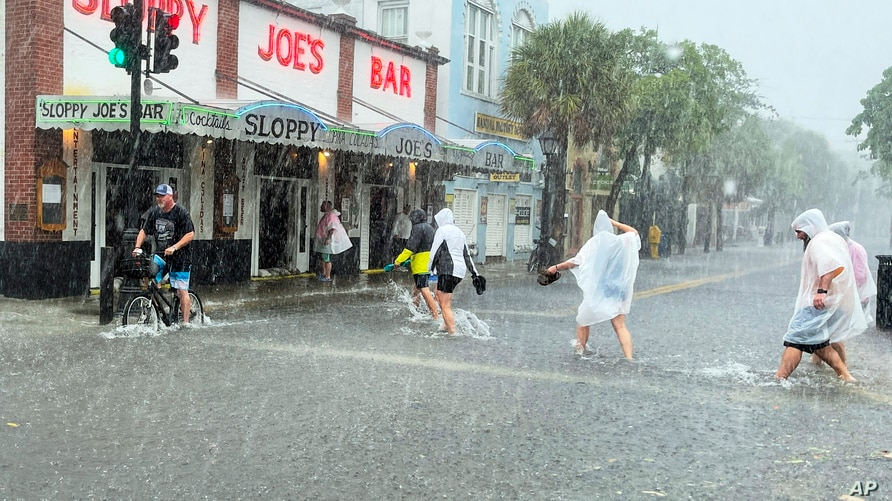 Determined visitors head for Sloppy Joe's Bar while crossing a flooded Duval Street as heavy winds and rain pass over Key West,…
