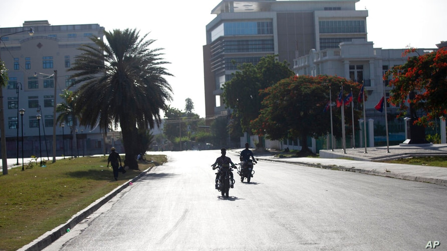 People ride their motorcycles on a street empty of traffic near the National Palace in Port-au-Prince, Haiti, Wednesday, July 7…