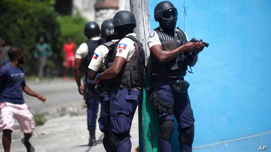 Police officers with their weapons drawn search for suspects in the murder Haiti's President Jovenel Moise, in Port-au-Prince,…