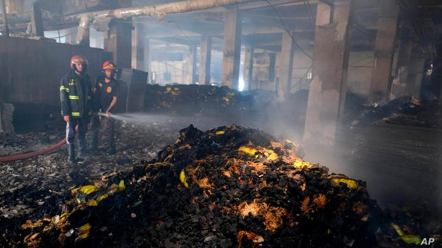 Firefighters work to douse a fire inside a food and beverage factory in Rupganj, outside Dhaka, Bangladesh,July 9.
