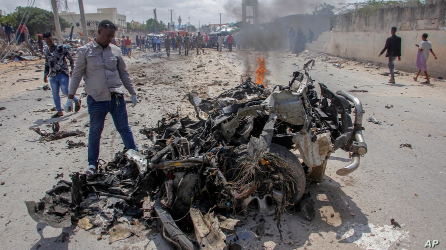 Security forces and civilians gather near the wreckage after a suicide car bomb attack that targeted the city's police commissioner in Mogadishu, Somalia, July 10, 2021.