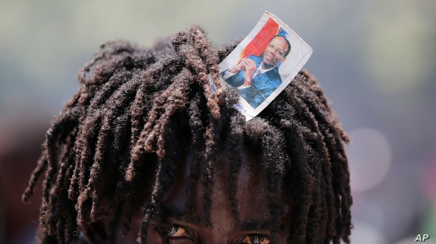 A supporter of former Haitian President Jean-Bertrand Aristide looks into the camera as he waits with others near the airport for his expected arrival from Cuba, where he underwent medical treatment, in Port-au-Prince, July 16, 2021.