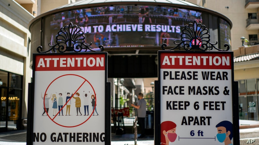 FILE - In this June 11, 2021, file photo, signs with social distancing guidelines and face mask requirements are posted at an…