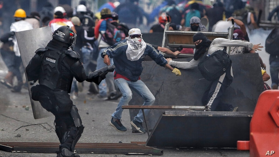 Demonstrators clash with the police during an anti-government protest in Cali, Colombia, Tuesday, July 20, 2021, as the county…