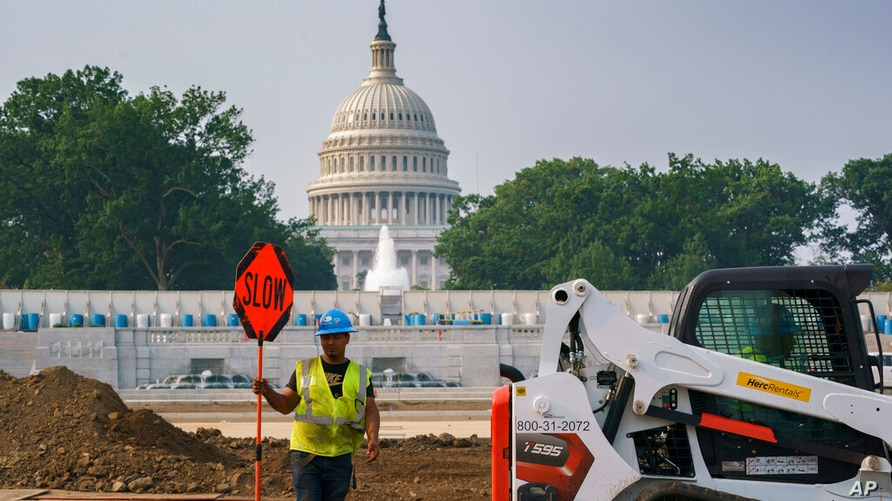 Workers repair a park near the Capitol in Washington, Wednesday, July 21, 2021, as senators struggle to reach a compromise over…