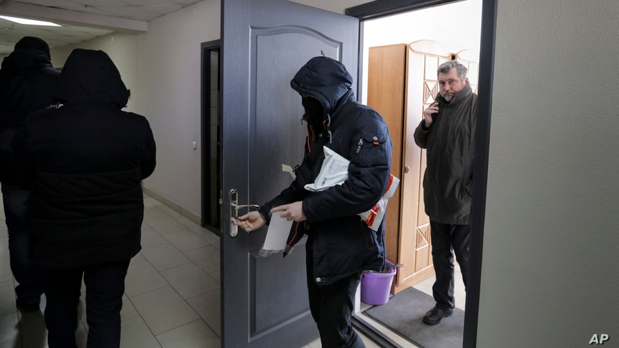FILE - Police carry documents and computers out of the office of the Belarusian Association of Journalists in Minsk, Feb. 16, 2021.