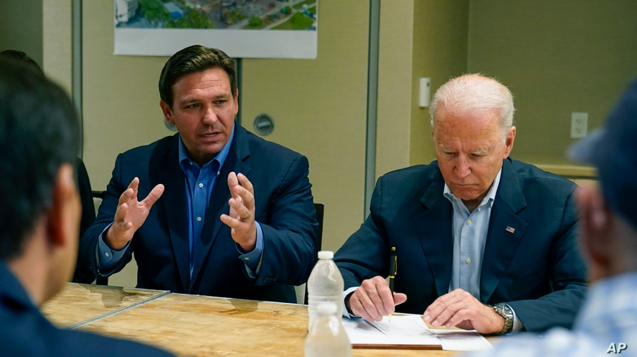 President Joe Biden listens as Florida Governor Ron DeSantis speaks during a briefing in Miami Beach, Florida, July 1, 2021, about the collapsed condo tower in Surfside.
